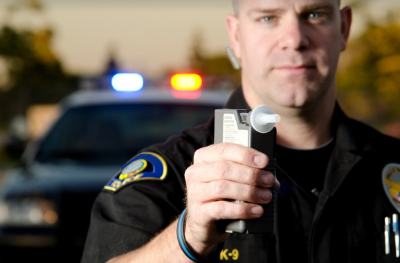 police officer giving a breathalyzer test for DUI