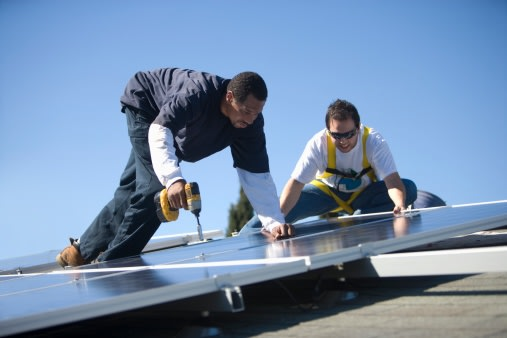 Two men working on solar panelling