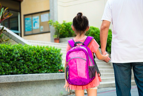 Parent taking child with a backpack to school.