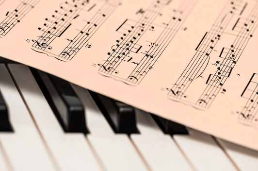 sheet music sitting on piano keys