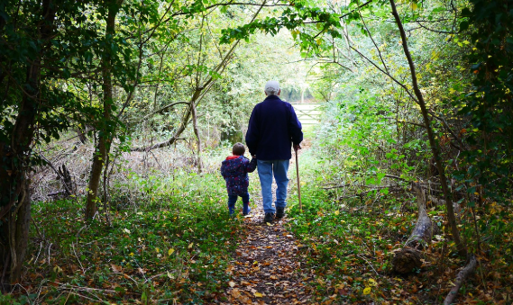 grandparent walking with grandchild on property