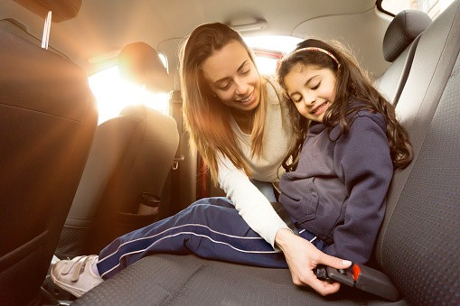 mother seatbelts daughter in car
