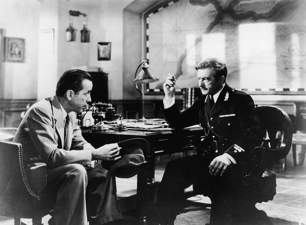 American actor Humphrey Bogart (left) (1899 - 1957) talks to British actor Claude Rains (1889 - 1967) at a cafe table in a still from the film, 'Casablanca,' directed by Michael Curtiz, 1942. (Photo by Warner Bros./Getty Images)