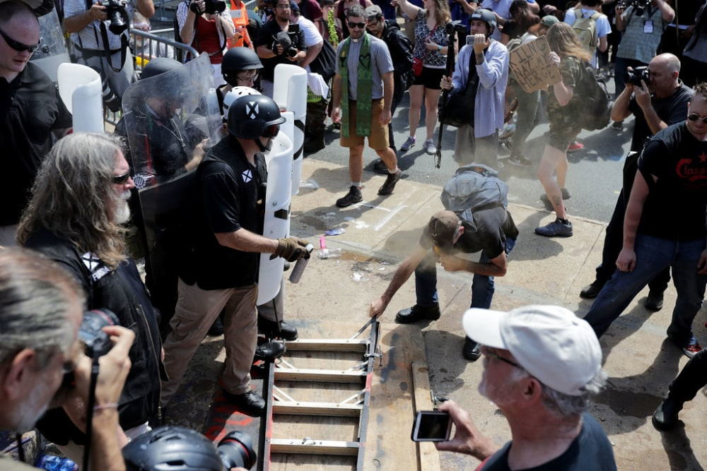 """CHARLOTTESVILLE, VA - AUGUST 12:  White nationalists, neo-Nazis and members of the """"alt-right"""" clash with counter-protesters as they attempt to guard the entrance to Emancipation Park during the """"Unite the Right"""" rally August 12, 2017 in Charlottesville, Virginia. After clashes with anti-fascist protesters and police the rally was declared an unlawful gathering and people were forced out of Emancipation Park, where a statue of Confederate General Robert E. Lee is slated to be removed.  (Photo by Chip Somodevilla/Getty Images)"""