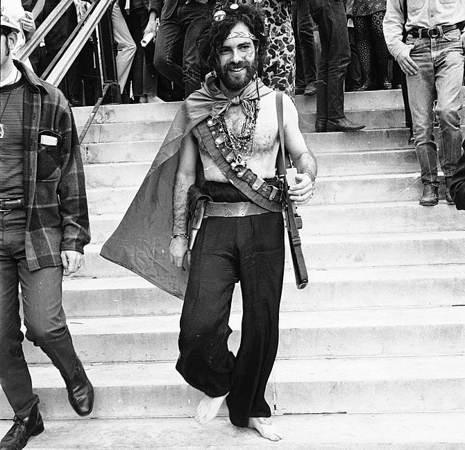 American activist Jerry Rubin (1938 - 1994) smiles as he walks down the steps barefoot outside the 1968 Democratic National Convention, Chicago, Illinois, August 1968. Rubin, who founded the Yippees political party, and six others, called the Chicago Seven, were indicted for conspiracy and inciting a riot during the convention. (Photo by Hulton Archive/Getty Images)