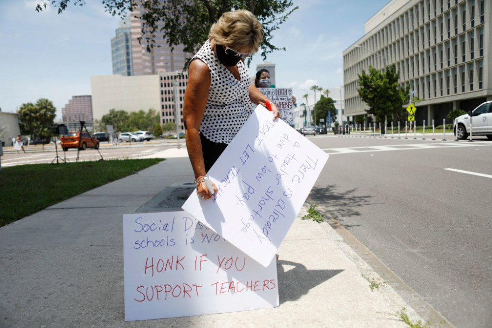 TAMPA, FL - JULY 16: High school math teacher Amy Eaglowski writes a message on a poster board while standing in protest in front of the Hillsborough County Schools District Office on July 16, 2020 in Tampa, Florida. Teachers and administrators from Hillsborough County Schools rallied against the reopening of schools due to health and safety concerns amid the COVID-19 pandemic. (Photo by Octavio Jones/Getty Images)