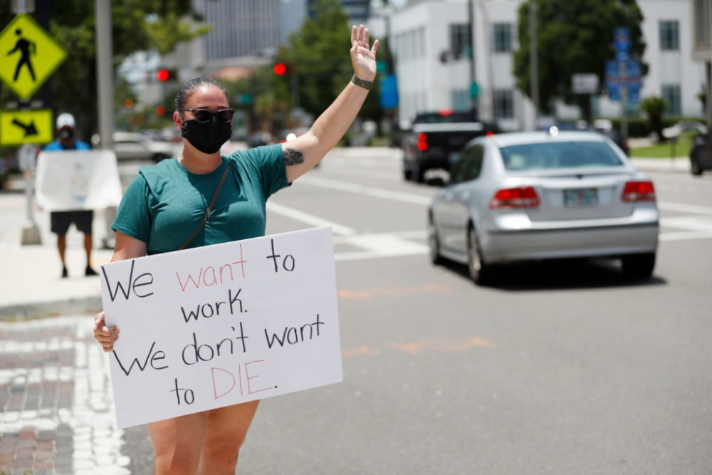 TAMPA, FL - JULY 16: Middle school teacher Danielle Weigand stands in protest in front of the Hillsborough County Schools District Office on July 16, 2020 in Tampa, Florida. Teachers and administrators from Hillsborough County Schools rallied against the reopening of schools due to health and safety concerns amid the COVID-19 pandemic. (Photo by Octavio Jones/Getty Images)