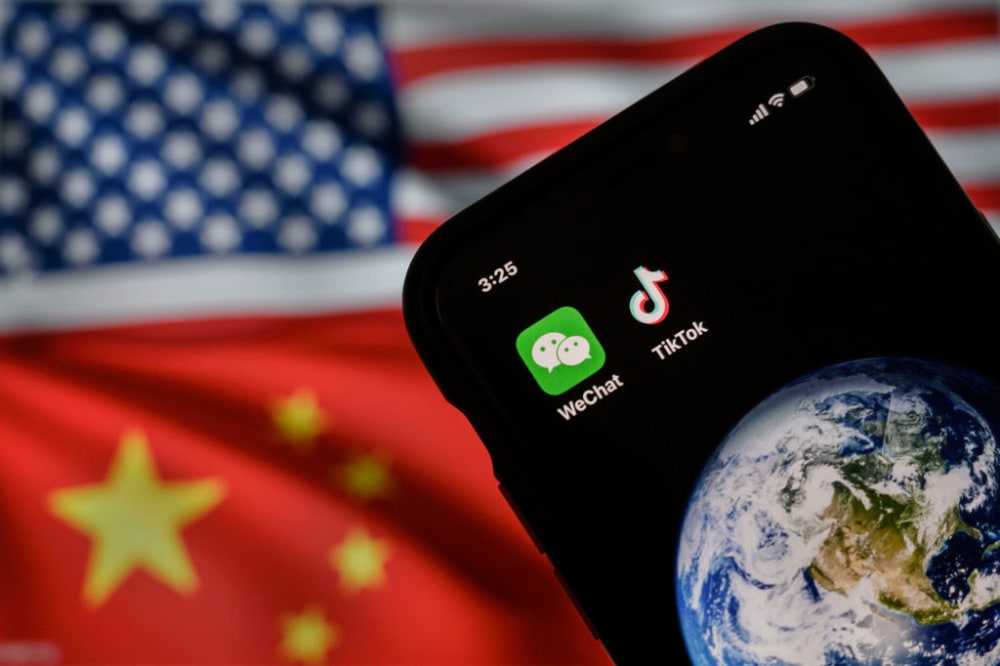 BEIJING, CHINA - SEPTEMBER 22: In this photo illustration, a mobile phone can be seen displaying the logos for Chinese apps WeChat and TikTok in front of a monitor showing the flags of the United States and China on an internet page, on September 22, 2020 in Beijing, China. Both popular Chinese-owned apps are facing bans under an executive order signed by United States President Donald Trump, but on Saturday, Trump said he was giving the go ahead to a deal between TikTok, Oracle, and Walmart and a judge in California issued a preliminary injunction blocking the administrations WeChat ban. (Photo by Kevin Frayer/Getty Images)