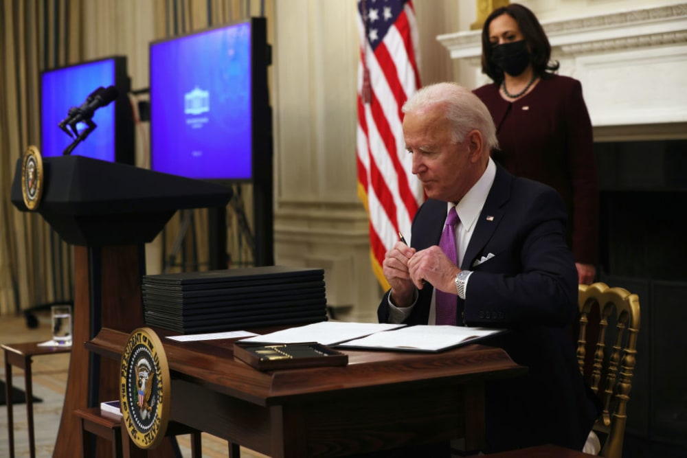WASHINGTON, DC - JANUARY 21: U.S. President Joe Biden signs executive orders as Vice President Kamala Harris looks on during an event at the State Dining Room of the White House January 21, 2021 in Washington, DC. President Biden delivered remarks on his administration�  s COVID-19 response, and signed executive orders and other presidential actions. (Photo by Alex Wong/Getty Images)