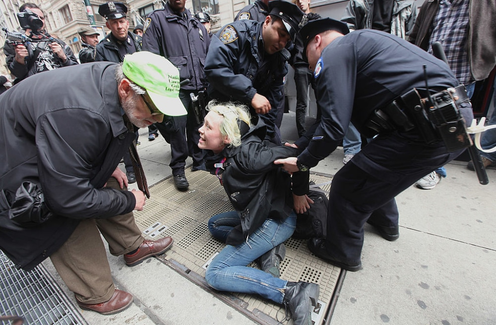 NEW YORK, NY - MAY 01:  A protester affiliated with Occupy Wall Street speaks to a representative from the National Lawyers Guild while being arrested during a march through lower Manhattan on May 1, 2012 in New York City. Occupy Wall Street has joined with unions during the May Day protests, a traditional day of global protests in sympathy with unions and leftist politics.   (Photo by Mario Tama/Getty Images)