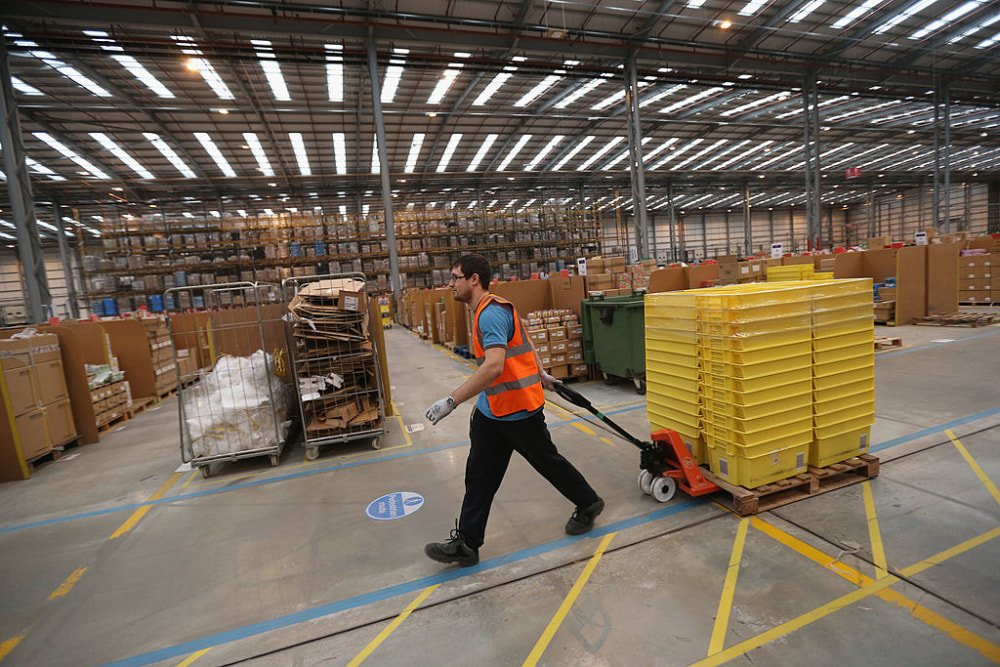 Employees select and dispatch items in an Amazon 'fulfilment centre' warehouse