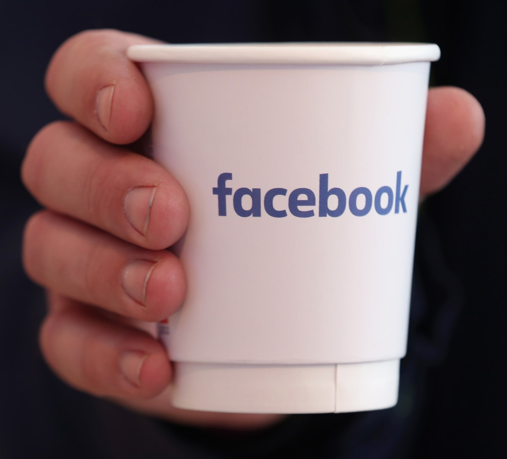 BERLIN, GERMANY - FEBRUARY 24:  A visitor holds a paper coffee cup adorned with the Facebook logo at the Facebook Innovation Hub on February 24, 2016 in Berlin, Germany. The Facebook Innovation Hub is a temporary exhibition space where the company is showcasing some of its newest technologies and projects.  (Photo by Sean Gallup/Getty Images)