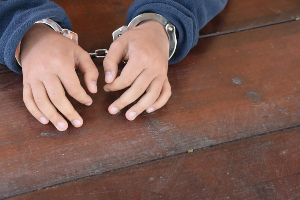 Child's hands in handcuffs