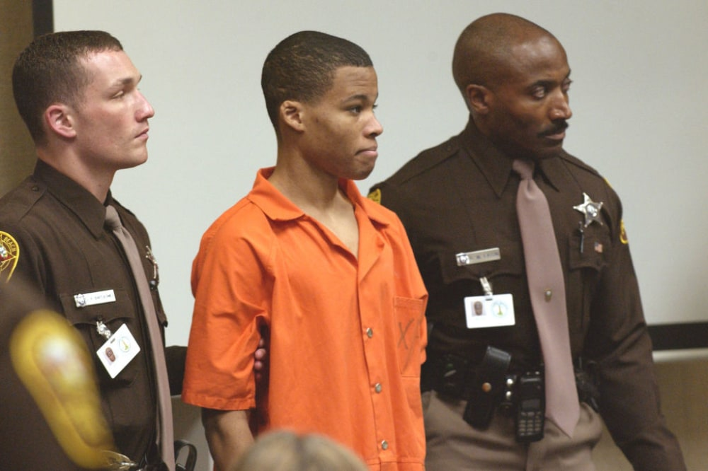 VIRGINIA BEACH, VA - OCTOBER 22:  Sniper suspect Lee Boyd Malvo (C) is escorted by deputies as he is brought into court to be identified by a witness during the murder trial in courtroom 10 at the Virginia Beach Circuit Court October 22, 2003 in Virginia Beach, Virginia. Muhammad has decided not to represent himself in court and to turn his defense back to his attorneys.  (Photo by Davis Turner-Pool/Getty Images)