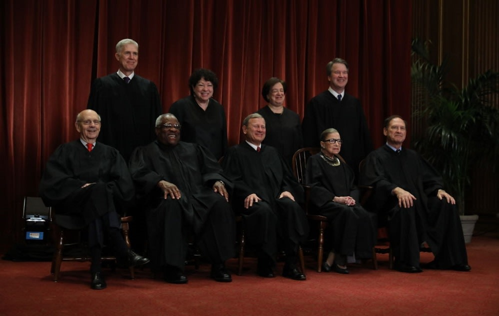 WASHINGTON, DC - NOVEMBER 30: United States Supreme Court (Front L-R) Associate Justice Stephen Breyer, Associate Justice Clarence Thomas, Chief Justice John Roberts, Associate Justice Ruth Bader Ginsburg, Associate Justice Samuel Alito, Jr., (Back L-R) Associate Justice Neil Gorsuch, Associate Justice Sonia Sotomayor, Associate Justice Elena Kagan and Associate Justice Brett Kavanaugh pose for their official portrait at the in the East Conference Room at the Supreme Court building November 30, 2018 in Washington, DC. Earlier this month, Chief Justice Roberts publicly defended the independence and integrity of the federal judiciary against President Trump after he called a judge who had ruled against his administration�  s asylum policy �  an Obama judge.�   �  We do not have Obama judges or Trump judges, Bush judges or Clinton judges,�   Roberts said in a statement. �  What we have is an extraordinary group of dedicated judges doing their level best to do equal right to those appearing before them. That independent judiciary is something we should all be thankful for.�   (Photo by Chip Somodevilla/Getty Images)