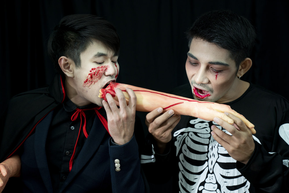 Two men in Halloween costumes pretending to eat a human arm.
