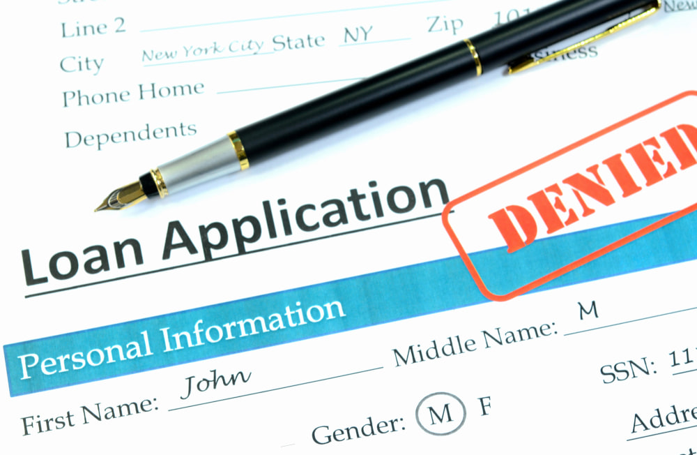 Loan application with denied stamp on it,