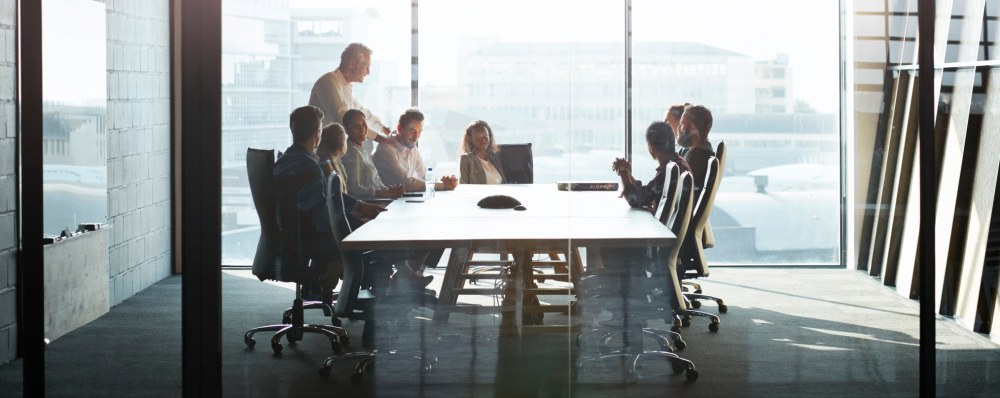 CEO giving peptalk to businesspeople at meeting in big conferenceroom