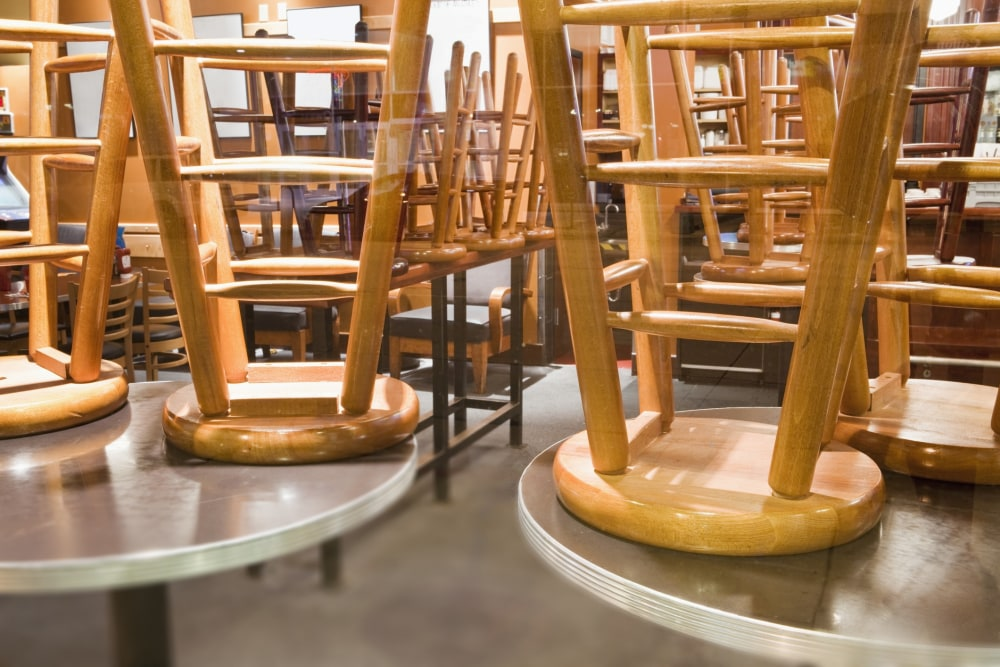 stools on top of tables in a closed restaurant