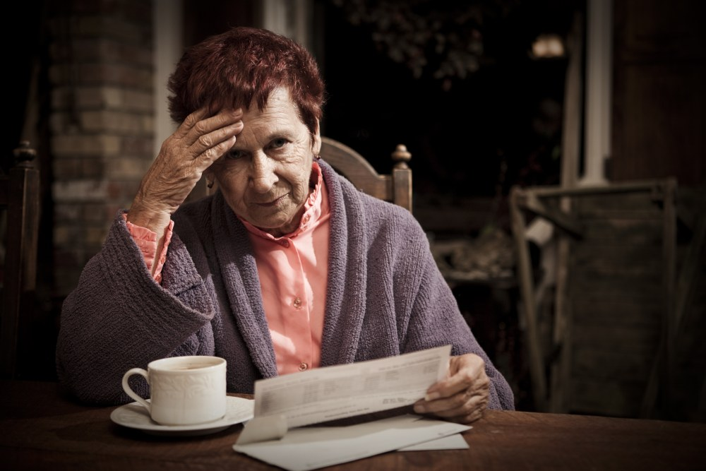 A senior woman seated at the table with a cup of coffee distressed over the costs of her bills.