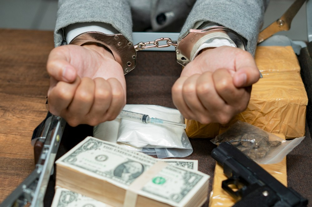 money, guns and drugs on a table with handcuffed wrists