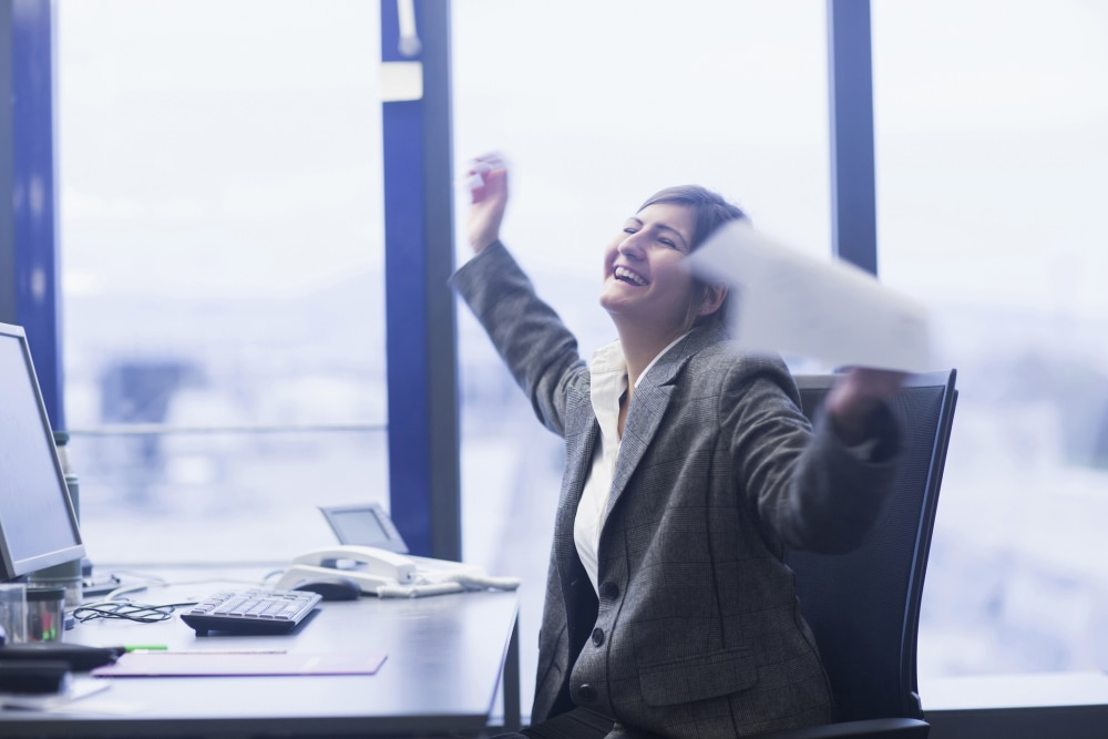 Excited lawyer celebrating her success in an office
