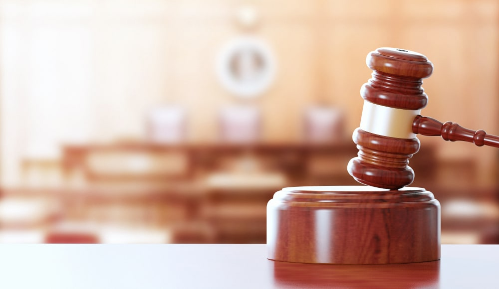 Wooden gavel in the foreground of a photo of an empty courtroom