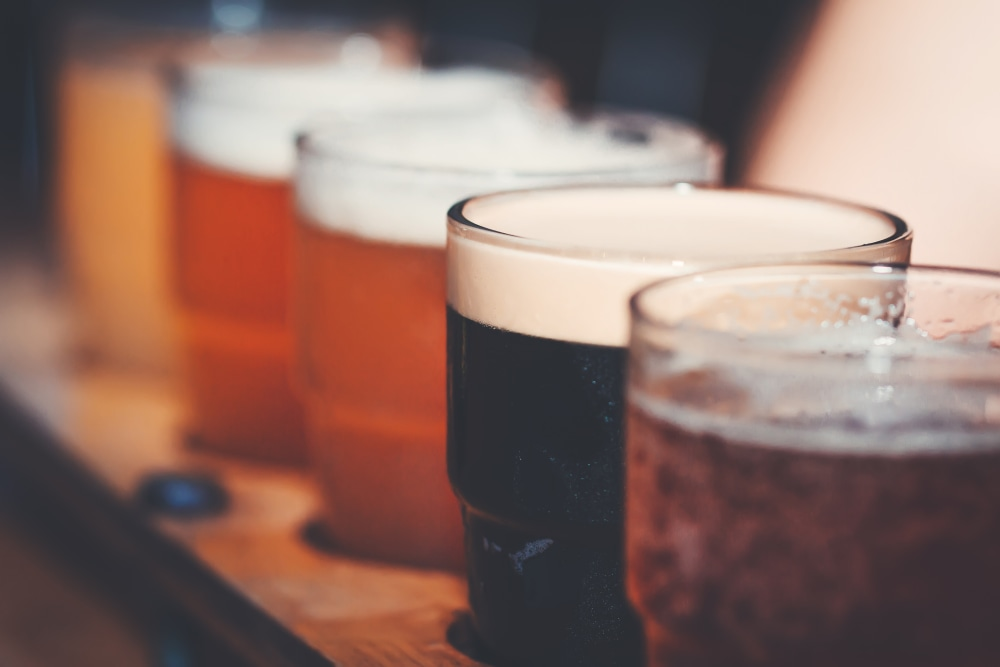 A close-up of various types of beer samplers in a row