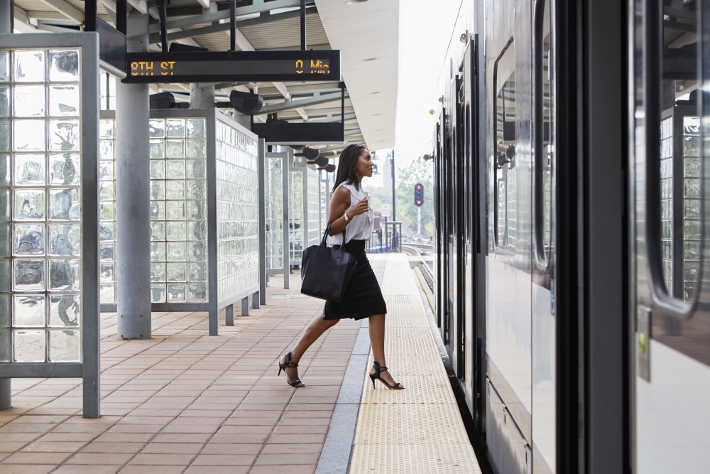 Female attorney with work bag stepping onto train.