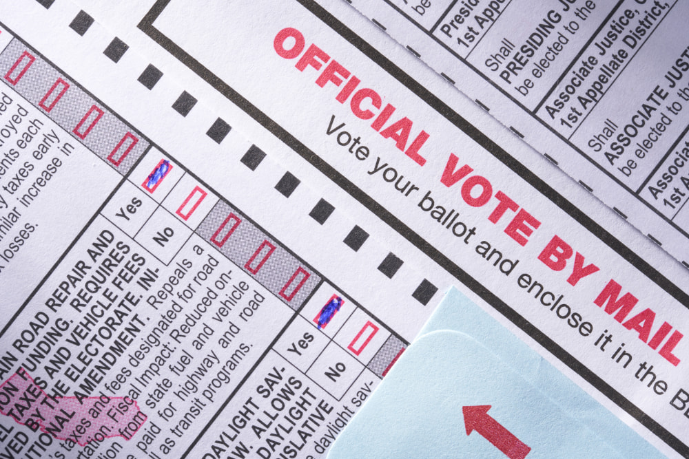 Voting ballot: Absentee voting by mail with candidates and measures on paper and pen with glasses