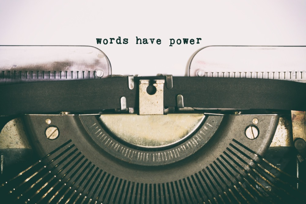 """Close-up of a typewriter with the phrase """"Words have power"""" typed on the page"""