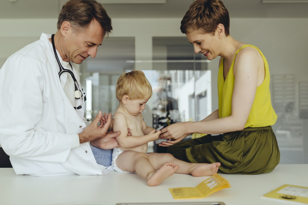 Doctor gives baby a vaccination while mom looks on.