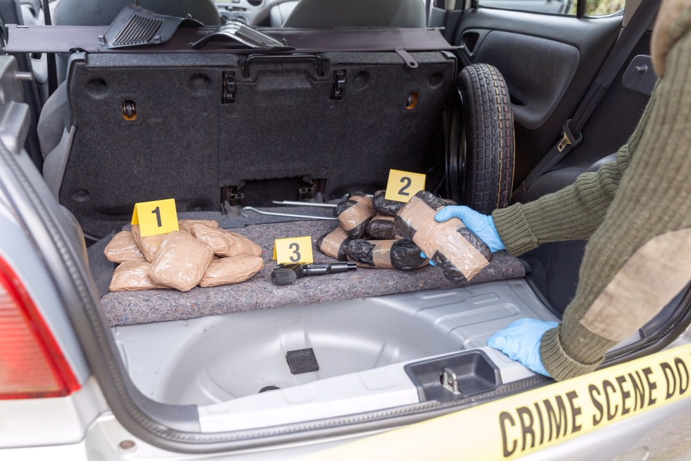 Police pull drugs out of a car at at crime scene