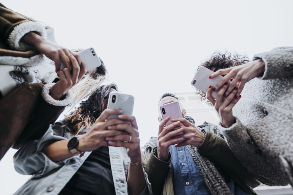 Group of friends in the street with smartphones