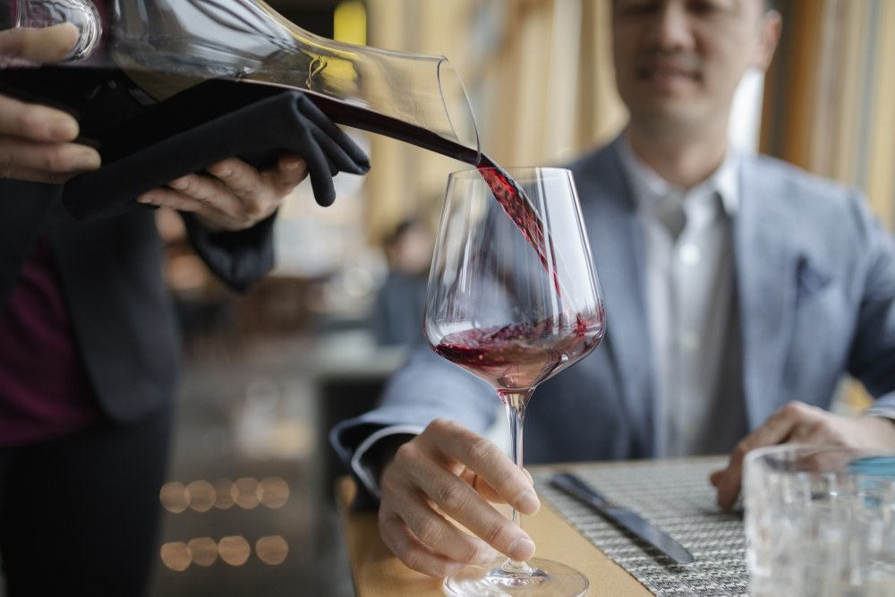 a waiter filling a glass of red wine
