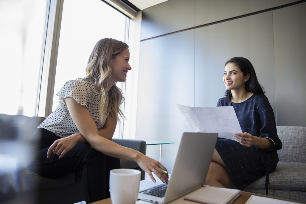 Two women in an office having a casual meeting