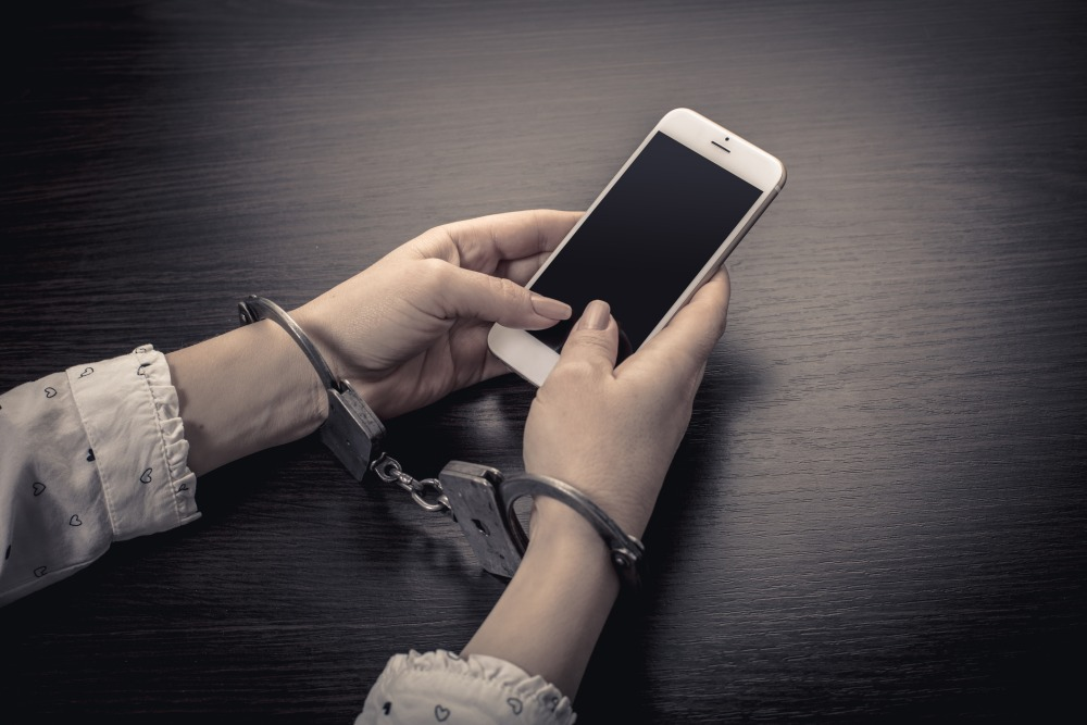 handcuffed hands with a mobile phone on wooden background