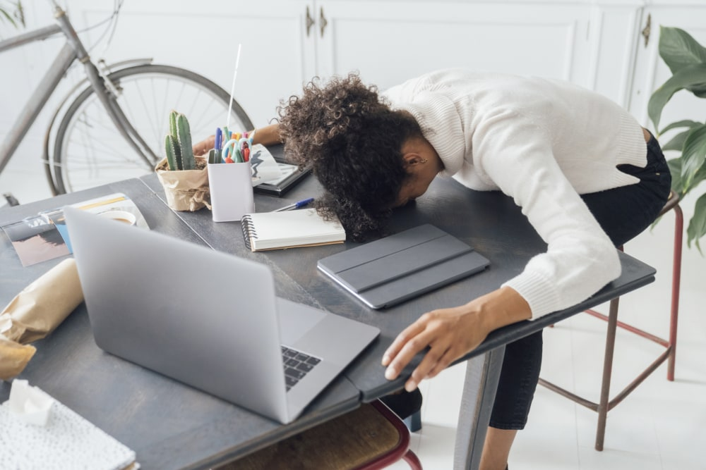 Overworked woman with her head resting on her desk