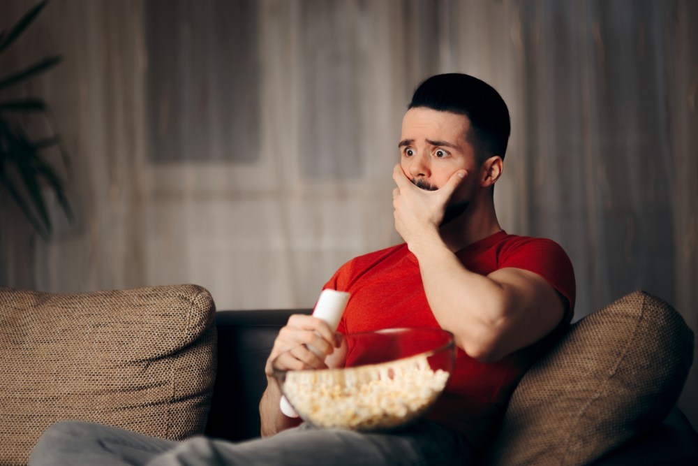 Young guy watching a dramatic show gasps with a hand to his face and a bowl of popcorn.