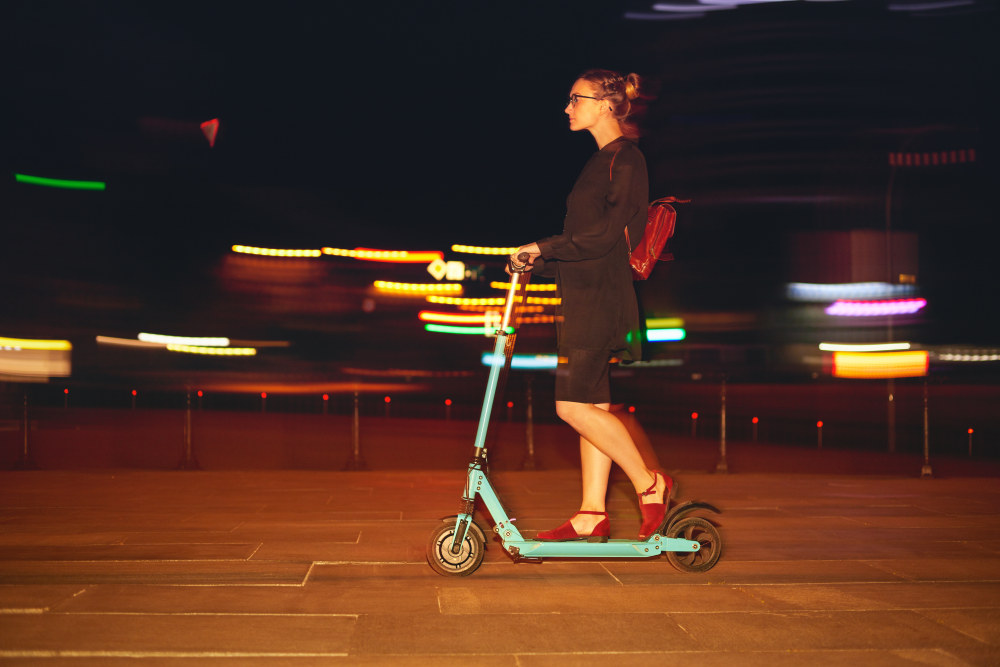 Woman in work attire with a backpack on an electric scooter at night.
