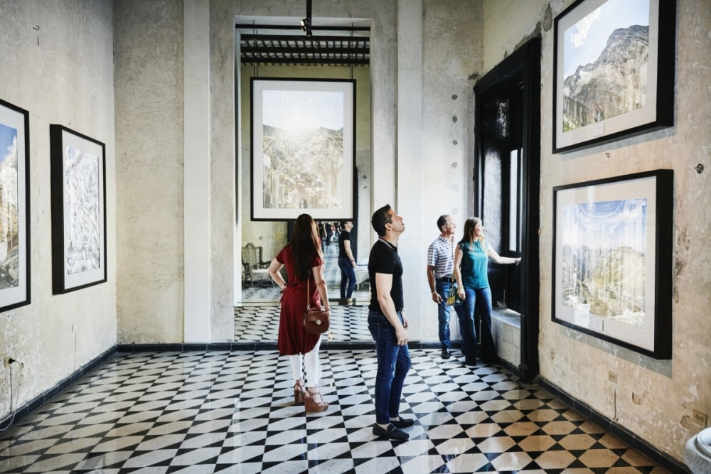 People standing in an art gallery admiring paintings on the walls