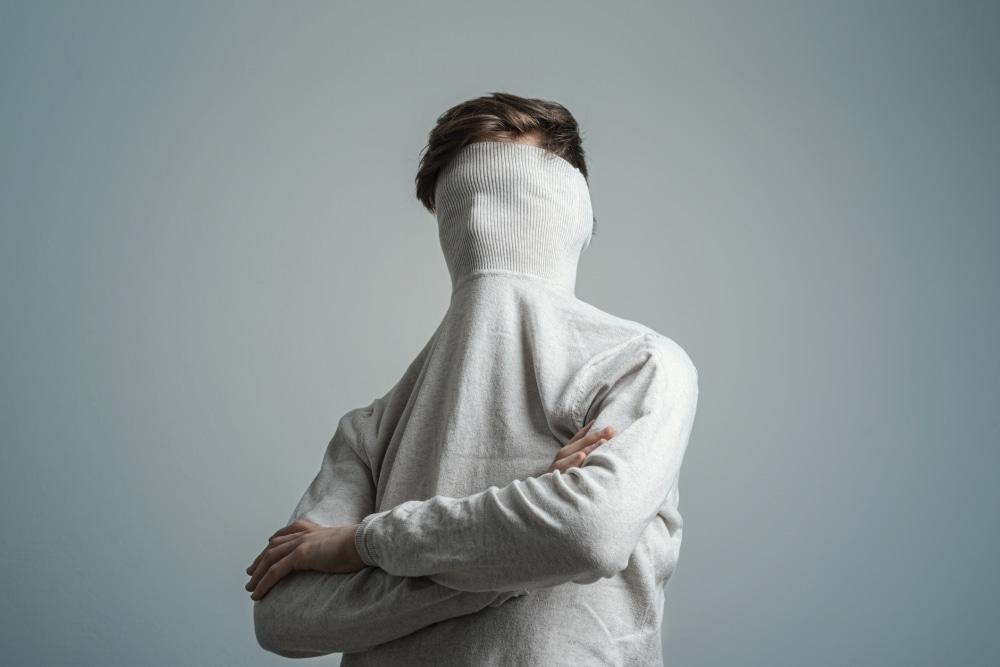 Young man with a face hidden by a white sweater