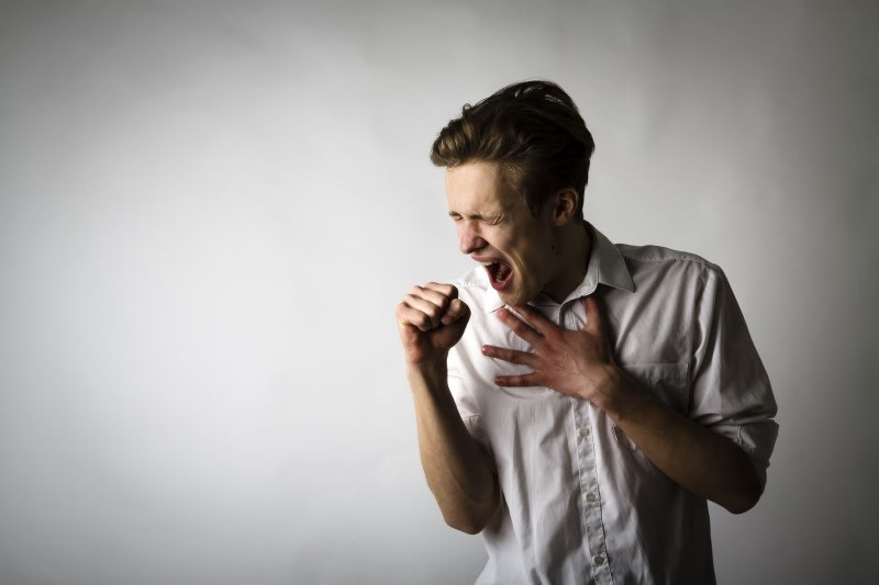 A man against a white background making a big cough while trying to cover his mouth
