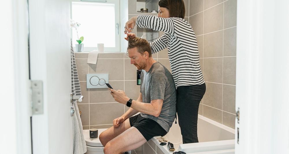 Spouse cutting hair in bathroom during pandemic