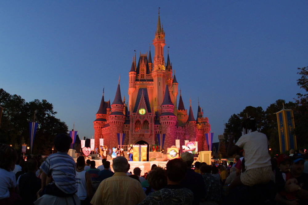 Disney Castle Night ORLANDO, FL - NOVEMBER 11:  (FILE PHOTO)  People watch a show on stage in front of Cinderella's castle at Walt Disney World's Magic Kingdom November 11, 2001 in Orlando, Florida. Health officials said a salmonella outbreak at Walt Disney World sickened as many as 141 people, including visitors attending an athletic competition for organ-transplant recipients August 23.  (Photo by Joe Raedle/Getty Images)