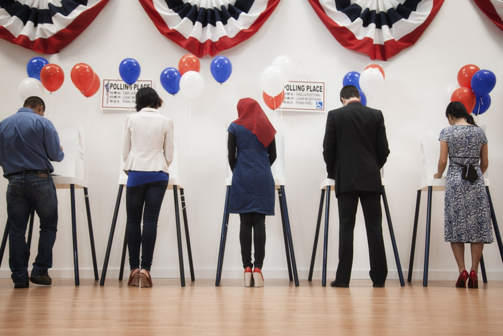 A line of five voters casting their ballots at their polling place, with red white and blue half circle banners above their heads.