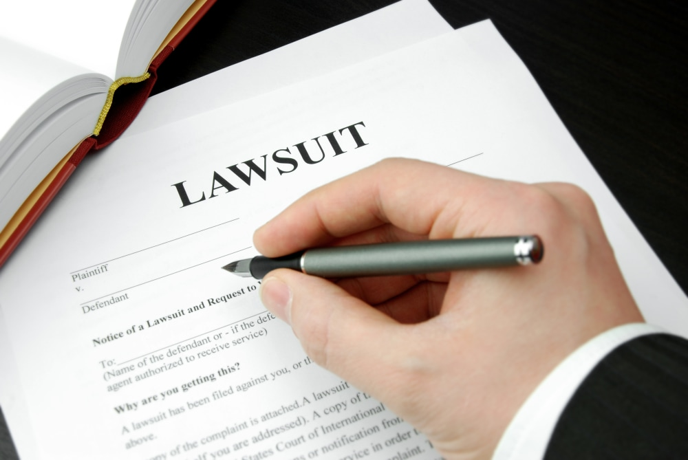 lawsuit form with attorney's hand and pen