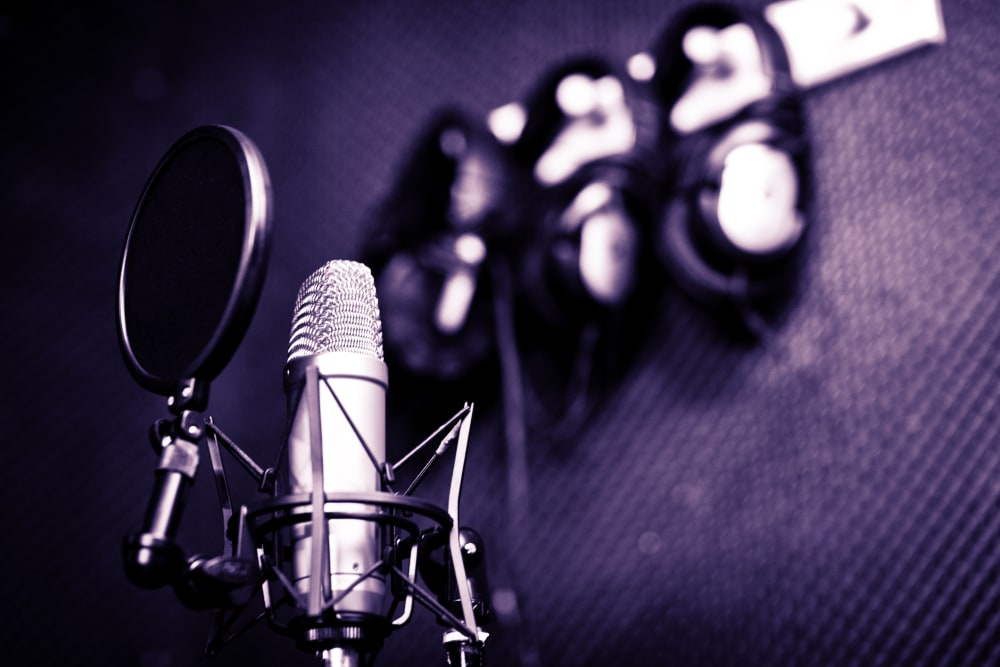 Microphone with pop filter and headphones hanging up in the background.