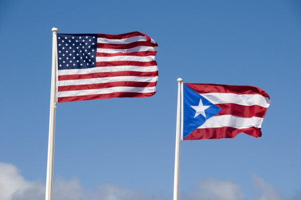 The United States flag flying in the breeze next to the flag of Puerto Rico