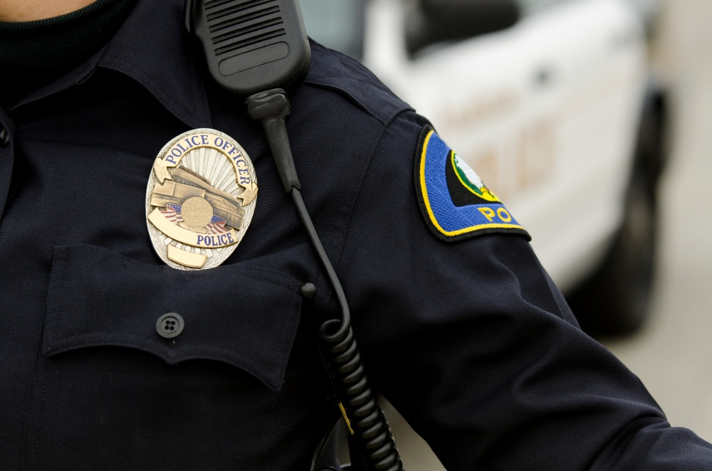 a close up of an officers uniform and badge with a patrol car in the background.